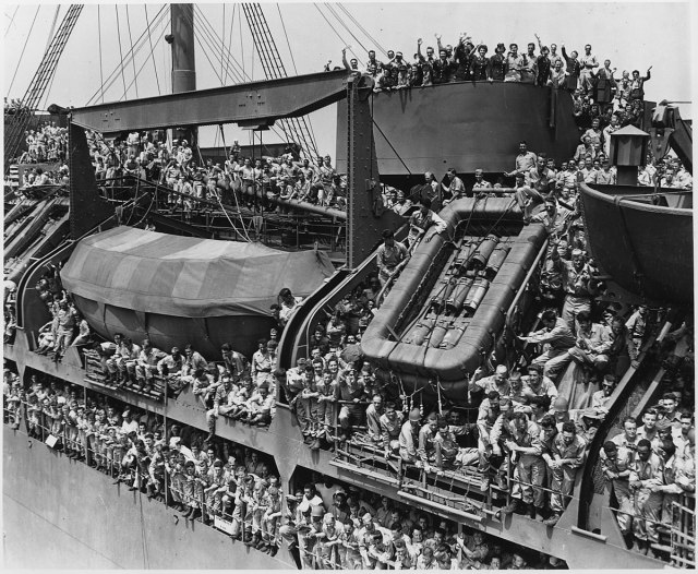1200px-US_troops_aboard_the_USS_Gen._Harry_Taylor_reverse_their_route_back_to_NY._-_NARA_-_195339